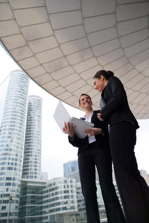 Two businesswomen stood outside high-rise building photo