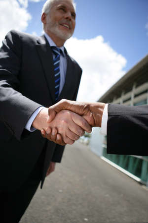 all smiles: mature businessman all smiles shaking hands with male counterpart Stock Photo