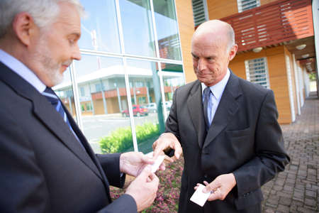Senior businessmen exchanging cards photo
