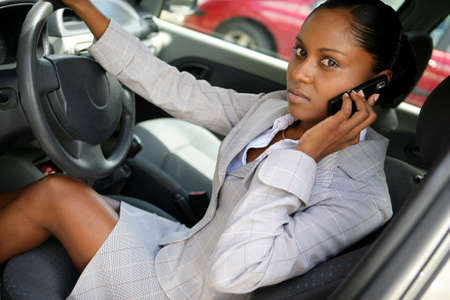 Woman talking on her mobile phone in her car photo