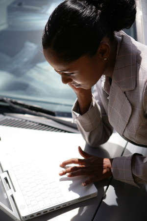Businesswoman using laptop on her car bonnet photo