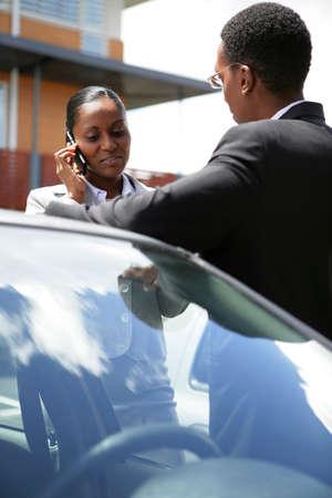 Car salesman with female customer photo