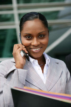 Businesswoman stood with cellphone and folders Stock Photo - 13828147