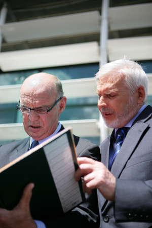 Senior businessmen looking at a folder photo