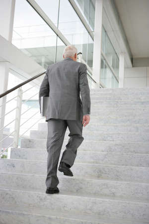 Grey-haired businessman climbing steps photo