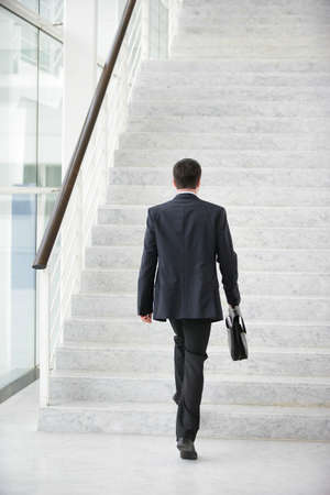 Businessman going upstairs photo