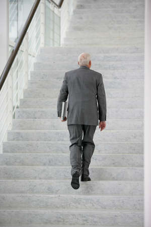 steps to success: senior businessman climbing the stairs