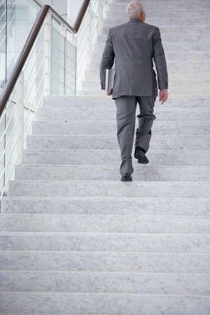 climbing ladder: Businessman going upstairs Stock Photo