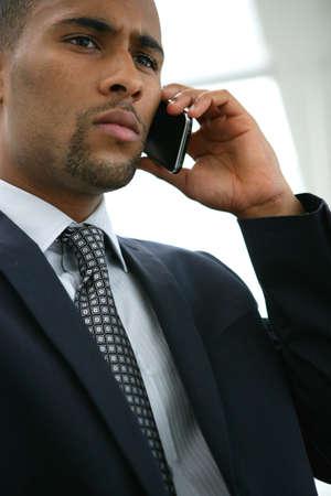african man: Serious businessman using a cellphone