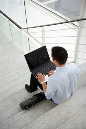 Businessman sitting on some steps with a laptop photo
