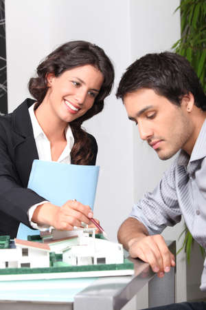 businesswoman showing a model of a house to a client photo