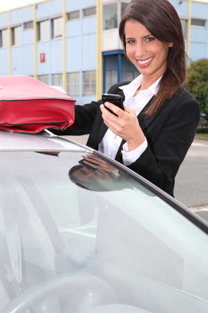 Woman with a phone by her car photo