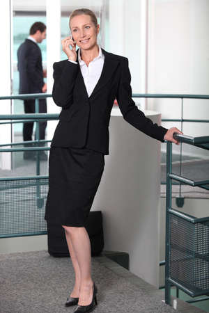 skirt suit: Woman in a skirt suit on cellphone