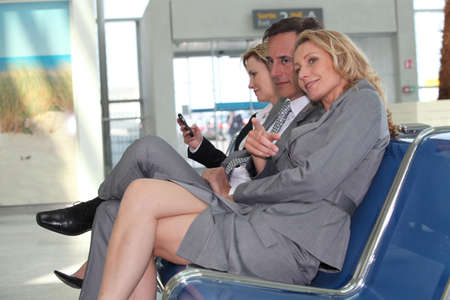 Businessmen and women in departure lounge photo