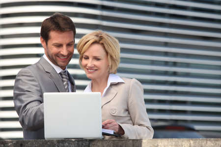 Businessman and woman looking at laptop Stock Photo - 13845490