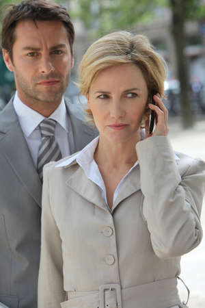Businessman and woman using phone. photo