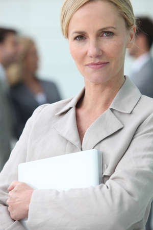 Smart blonde woman holding a laptop computer Stock Photo - 13845999