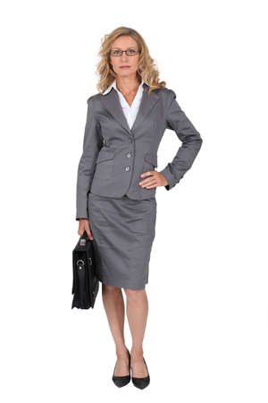 attire: Woman in a business suit with her hand on her hip Stock Photo