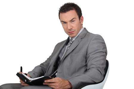 reviewer: Man in suit writing in diary