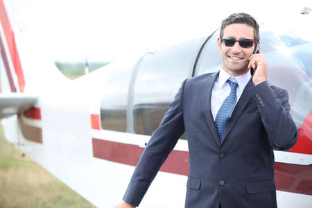 Executive chatting on the phone in front of a small aeroplane photo