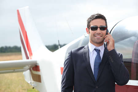 moneyed: Man talking on a mobile phone next to a private plane Stock Photo