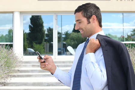 Businessman stood outdoors sending text message from telephone photo