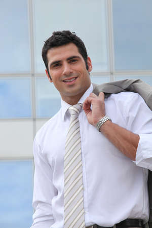 Businessman holding his suit jacket over his shoulder photo