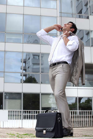 Businessman laughing on his cellphone outside an office building photo