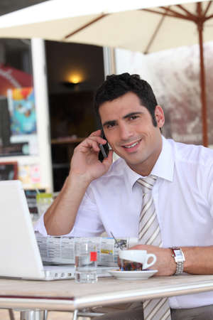 shirtsleeves: Businessman drinking an expresso in a cafe while talking on a cellphone