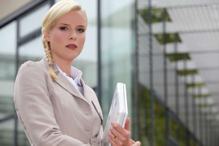 Blond businesswoman holding laptop computer outside glass building Stock Photo - 13841933
