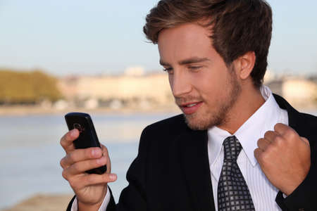 Young executive pleased with his phone message photo