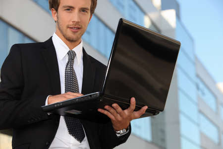 Young business outside office with laptop computer Stock Photo - 13839553