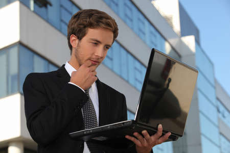 Handsome businessman using a laptop in the city Stock Photo - 13839622