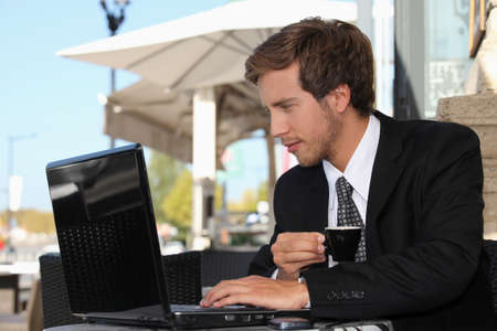 business man drinking coffee and watching his laptop on a street cafe photo
