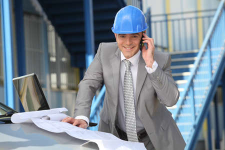 Engineer with architectural plans and cellphone Stock Photo - 13841803