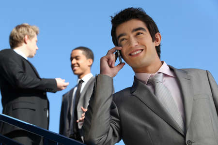 junior businessman on the phone outdoors photo