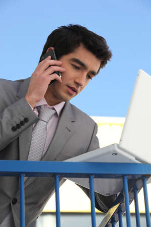 telephone salesman: Young businessman outside an office building