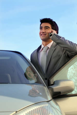 Businessman stood by his car making telephone call photo