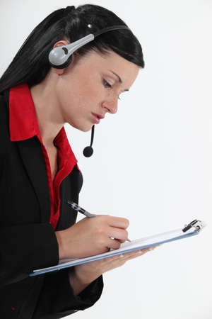 Young woman with headset and notepad Stock Photo - 13839401