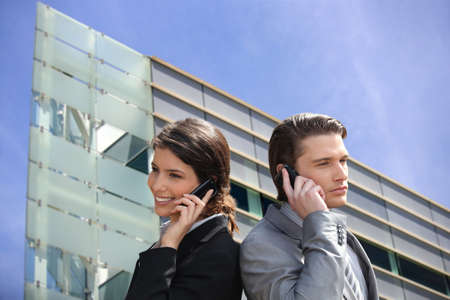 Montage of business couple in front of a modern building photo