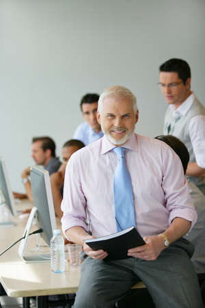 executive affable: Senior manager sitting on a desk in front of his team