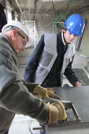 Two manual workers cutting sheet metal photo