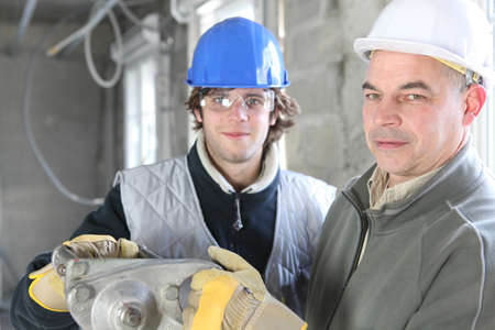 Construction worker and young helper photo