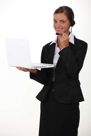 Woman holding laptop and wearing telephone head-set photo