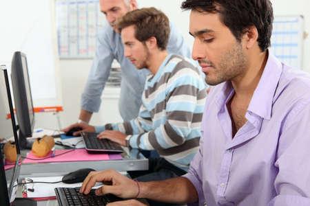 office worker: Los hombres j�venes que trabajan en los equipos