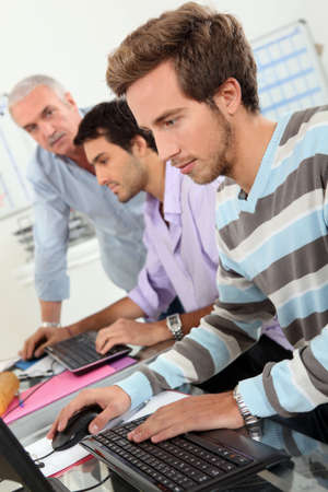 Young men using computers photo