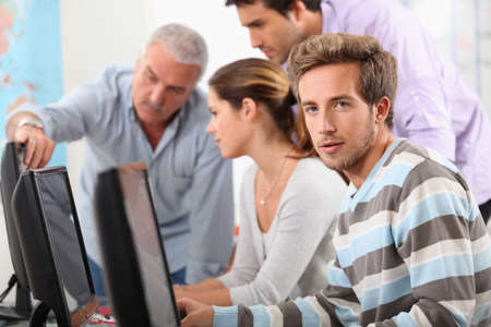undergrad: Teacher and students gathered around computer screen Stock Photo