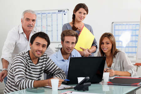 Class and teacher gatherd around laptop Stock Photo - 13839964