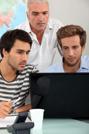 Men sitting around a laptop photo