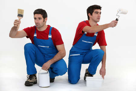 unison: Two male decorators working in unison